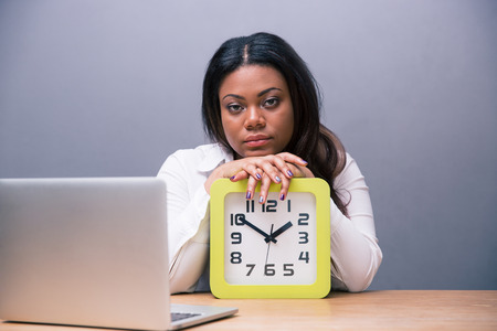 Tired african businesswoman sitting at the table with clock and laptop over gray background. Looking at camera photo