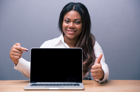 Happy african businesswoman sitting at the table and pointing on blank laptop screen over gray background photo