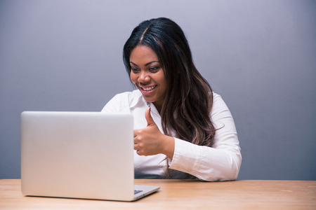 Happy african businesswoman sitting at the table with laptop and showing thumb up over gray background photo