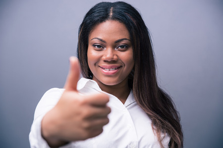 Smiling african businesswoman showing thumb up over gray background. Looking at camera photo
