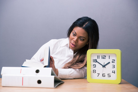African businesswoman sitting at the table with book and clock over gray background photo