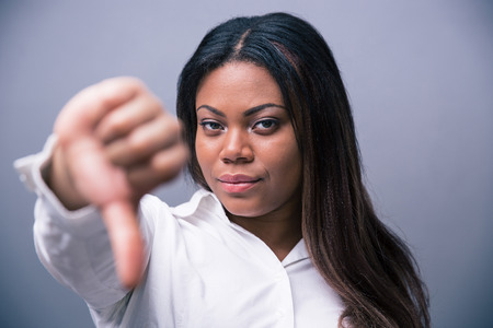 African businesswoman showung thumb down over gray background photo