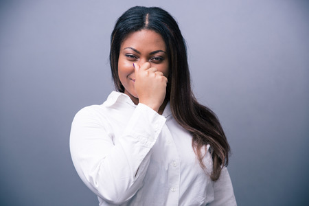 detestable: African businesswoman covering her nose over gray background and looking at camera Stock Photo