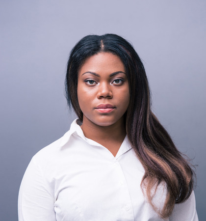 Portret van een ernstige Afrikaanse onderneemster over grijze achtergrond. Kijken naar de camera