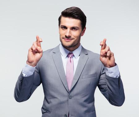De gelukkige zakenman met vingers kruiste over grijze achtergrond. Kijkend naar de camera Stockfoto