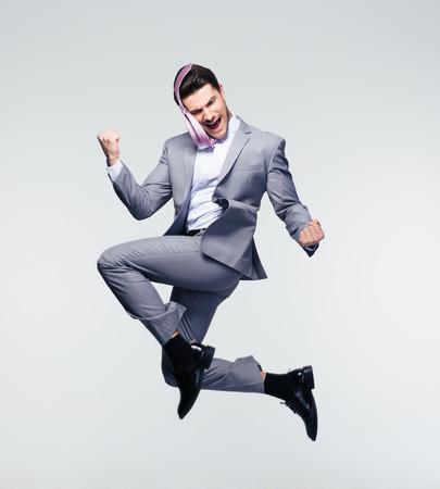 Gelukkig zakenman springen in de lucht over grijze achtergrond