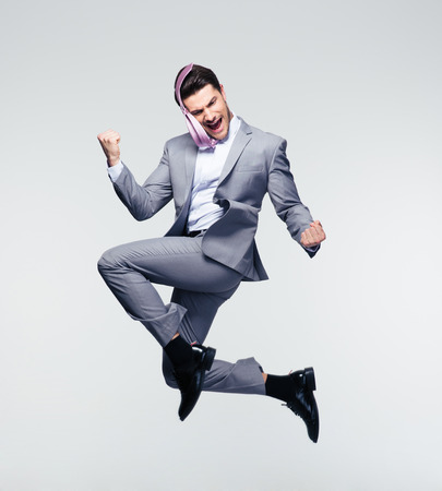 full suit: Happy businessman jumping in air over gray background
