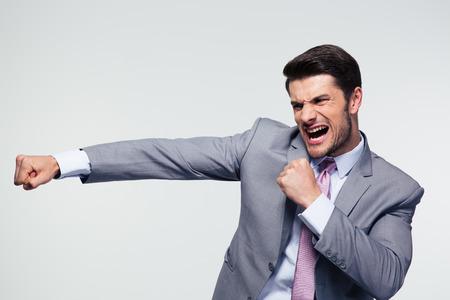 Boze zakenman vechten en schreeuwen over grijze achtergrond Stockfoto