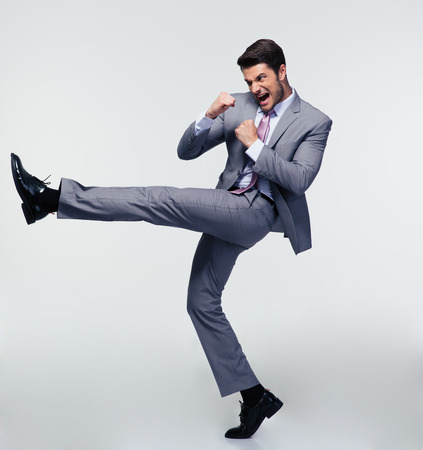 Full length portrait of handsome businessman kicking over gray background