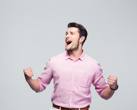 Hombre de negocios joven que celebra su éxito sobre fondo gris Foto de archivo