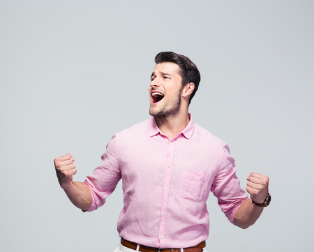 celebrates: Young businessman celebrating his success over gray background Stock Photo