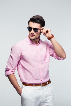 gafas de sol: Retrato de un hombre joven de moda en gafas de sol y una camisa de color rosa sobre fondo gris