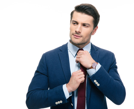 Handsome businessman straightening his tie isolated on a white background photo