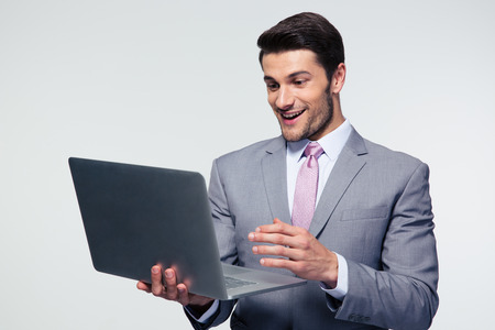 executive: Happy businessman using laptop over gray background