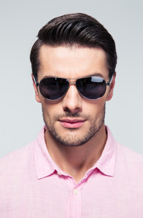 man relax: Portrait of a handsome fashion young man in sunglasses looking at camera over gray background Stock Photo