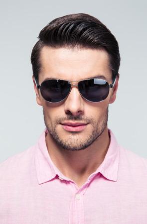gafas de sol: Retrato de un hombre joven y guapo de moda en gafas de sol mirando a la cámara sobre fondo gris