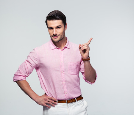 looking away from camera: Confident businessman in shirt pointing finger away over gray background. Looking at camera Stock Photo