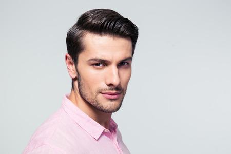 Retrato del primer de un hombre joven confidente en camisa sobre fondo gris. Mirando a la cámara