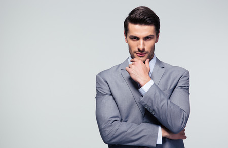 灰色の背景に彼のあごに触れて物思いにふけるビジネスマンの肖像画