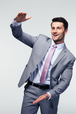 handsign: Happy businessman bragging about the size of something over gray background. Looking at camera