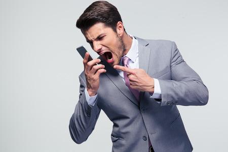 灰色の背景上で携帯電話で叫んで怒っているビジネスマン