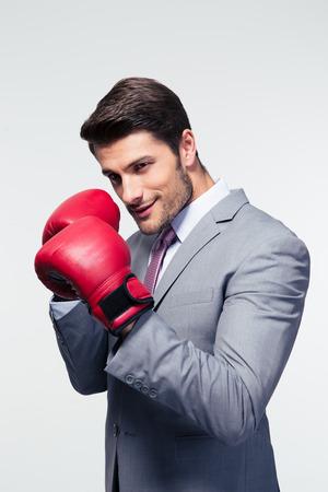 guantes de box: Hombre de negocios listo para luchar con los guantes de boxeo sobre fondo gris. Mirando a la cámara Foto de archivo