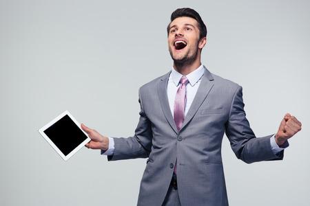 celebração: Homem de negócios feliz que comemora seu sucesso sobre o fundo cinzento