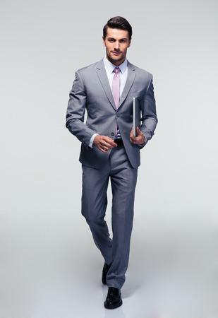 Volledige lengte portret van een zakenman lopen met latpop over grijze achtergrond Stockfoto