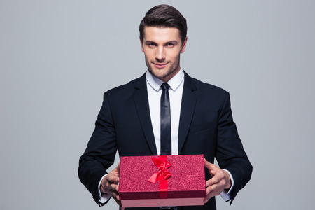 Handsome businessman holding gift box over gray background and looking at camera Stock Photo