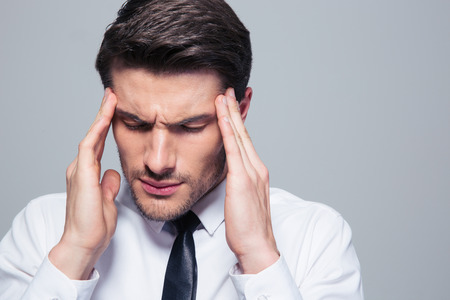 Pain Management: Businessman having headache over gray background Stock Photo