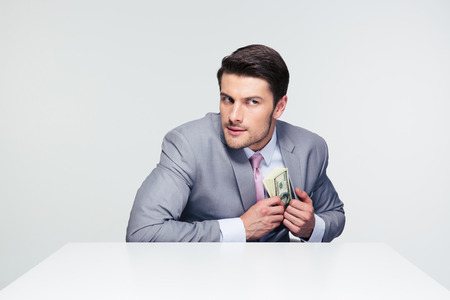 putting money in pocket: Businessman putting money in pocket over gray background and looking away Stock Photo