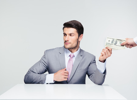 venal: Businessman sitting at the table and taking bribe over gray background. Looking away