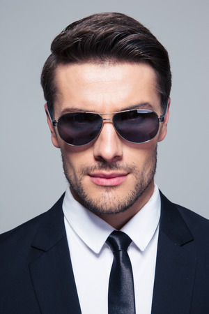 man with glasses: Handsome fashion businessman in sunglasses looking at camera over gray background Stock Photo