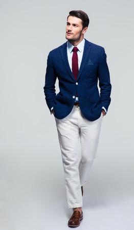 Full length portret van een knappe peinzende zakenman lopen over grijze achtergrond