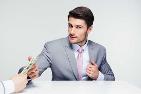 venal: Businessman sitting at the table and taking bribe over gray background. Looking at camera