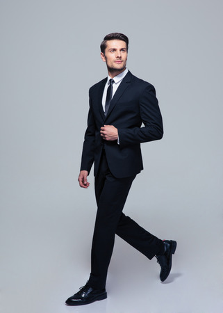 Full length portrait of a confident businessman walking over gray background