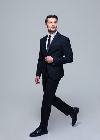 Volledige lengte portret van een zelfverzekerde zakenman lopen over grijze achtergrond Stockfoto