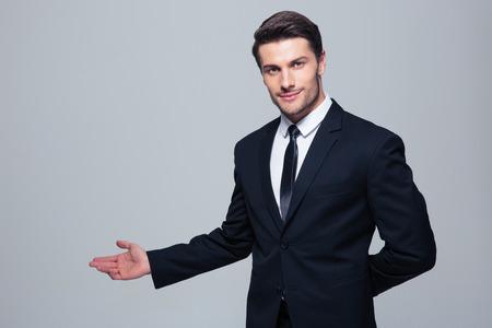 the welcome: Hombre de negocios con el brazo en un gesto de bienvenida sobre fondo gris