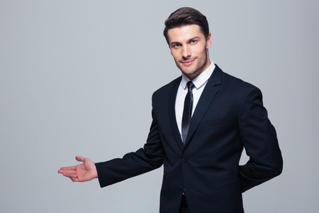 Zaken man met arm in een gastvrije gebaar over grijze achtergrond