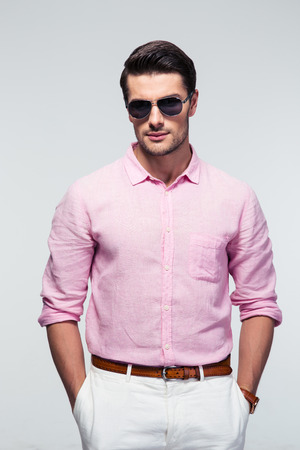 fashion model: Portrait of a trendy man in sunglasses over gray background. Looking at camera Stock Photo