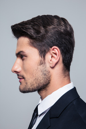 young office workers: Side view portrait of a handsome businessman over gray background