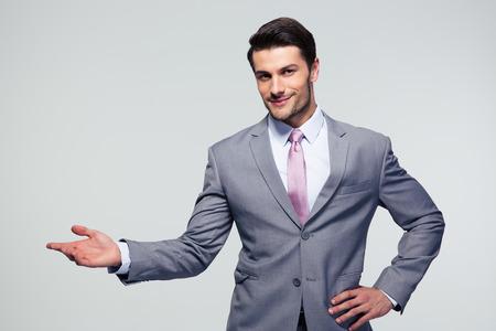 to gestures: Hombre de negocios con el brazo en un gesto de bienvenida sobre fondo gris