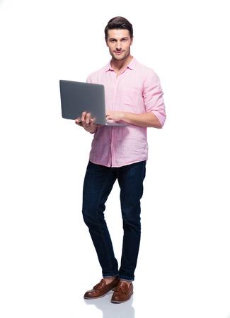 Full length Portret van een jonge man met behulp van laptop geïsoleerd op een witte achtergrond. Kijkend naar de camera