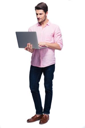 Jonge man staande en met behulp van laptop Isolataed op een witte achtergrond Stockfoto