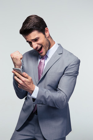 Happy businessman holding smartphone and celebrating his success over gray background