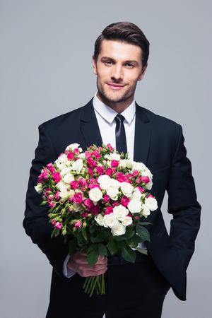 Apuesto hombre de negocios la celebración de flores sobre fondo gris y mirando a cámara
