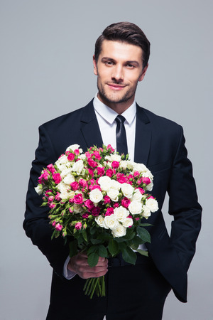 Handsome businessman holding flowers over gray background and looking at camera Stock Photo