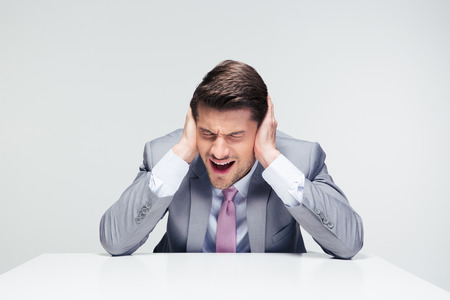 dissapointed: Dissapointed businessman sitting at the table and covering his ears over gray background Stock Photo