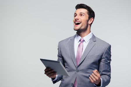 Cheerful businessman holding tablet computer over gray background