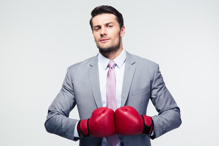 boxing knockout: Handsome businessman standing with boxing gloves over gray background. Looking at camera